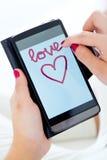 Mãos fêmeas usando seu smartphone em casa Fotos de Stock Royalty Free