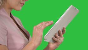 Mãos fêmeas usando a tabuleta em uma tela verde, chave do croma video estoque