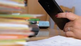 Mãos fêmeas usando um smartphone no desktop com originais e papéis video estoque