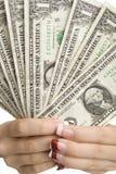 Mãos femininos que prendem o dinheiro Foto de Stock Royalty Free