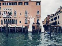 Mãos gigantescas que aumentam da água para apoiar o hotel de Ca' Sagredo, Veneza fotografia de stock