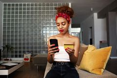 Mãos guardando fêmeas do cartão e do telefone celular de crédito das mãos do africano negro atrativo novo Tecnologia, Internet ba imagem de stock