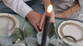 Mãos guardando nervosas entusiasmados dos pares românticos novos na amiga do noivo da tabela em casa vídeos de arquivo