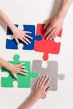 Mãos humanas em partes coloridas do enigma Fotos de Stock Royalty Free
