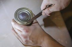Mãos humanas que abrem uma lata do leite condensado foto de stock royalty free