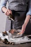 Mãos humanas que adicionam o açúcar aos ingredientes para fazer cookies Imagens de Stock Royalty Free