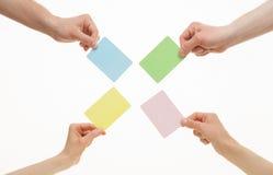 Mãos humanas que guardam cartões de papel coloridos Fotografia de Stock Royalty Free