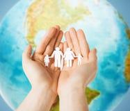 Mãos humanas que guardam a família de papel sobre o globo da terra fotografia de stock