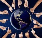 Mãos humanas que mostram os polegares acima em torno do planeta da terra foto de stock