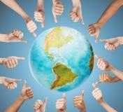 Mãos humanas que mostram os polegares acima no círculo sobre a terra Imagens de Stock