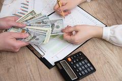 Mãos humanas que trocam o dinheiro acima do gráfico de negócio Imagem de Stock