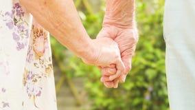 Mãos idosas da terra arrendada dos pares