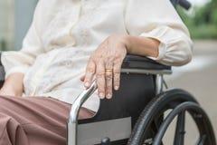 Mãos idosas em uma cadeira de rodas Fotos de Stock