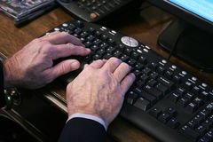 Mãos idosas no teclado Foto de Stock