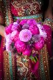 Mãos indianas das noivas que prendem o ramalhete Imagem de Stock