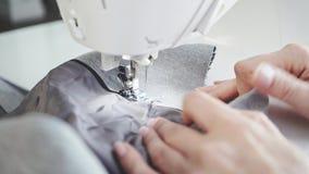 Mãos irreconhecíveis da jovem mulher com tratamento de mãos usando uma máquina de costura filme