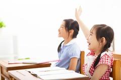 Mãos levantadas alunos na classe Fotografia de Stock