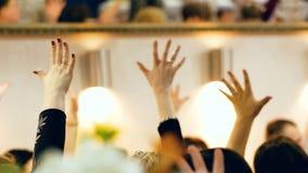 Mãos levantadas dos povos que sentam-se na tabela do feriado closeup video estoque