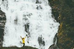 Mãos levantadas felizes do aventureiro da mulher que apreciam a cachoeira grande foto de stock royalty free