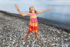 Mãos levantadas menina para cima na praia rochoso imagem de stock royalty free