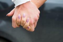 Mãos loving novas da terra arrendada dos pares Feche acima da vista Conceito do amor e dos relacionamentos fotos de stock