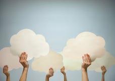 Mãos múltiplas que mantêm nuvens de papel cortadas contra um fundo azul, tiro do estúdio Fotografia de Stock
