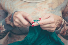 Mãos Manicured da mulher que fazem malha a manta verde Imagem de Stock Royalty Free