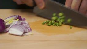 Mãos masculinas com a faca, cortando a cebola fresca grampo Corte da refeição em um fim da placa de madeira acima Mãos masculinas filme