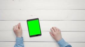 Mãos masculinas da vista superior que mostram gestos múltiplos na tabuleta digital com a tela verde na mesa branca de cima do esp filme