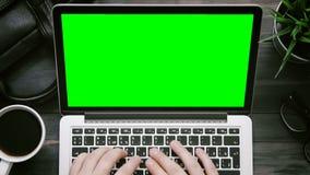 Mãos masculinas da vista superior que trabalham no laptop com a tela verde na mesa branca de cima de filme