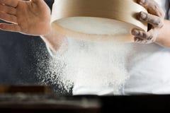 Mãos masculinas de um cozinheiro que peneira a farinha através de uma peneira na cozinha fotografia de stock
