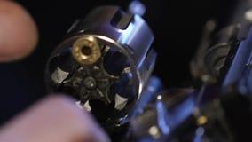 Mãos masculinas do bandido que carregam o close up do revólver, comércio ilícito da arma, prontidão video estoque