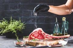 Mãos masculinas do bife do machado de guerra da terra arrendada do carniceiro ou do cozinheiro no fundo rústico escuro da mesa de fotos de stock royalty free