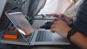 Mãos masculinas do close-up com relógio esperto usando o portátil para trabalhar em linha durante o voo confortável da viagem de  filme