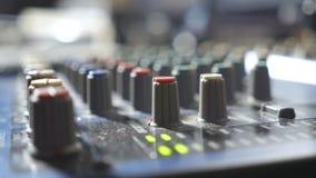 Mãos masculinas do coordenador sadio que ajustam os botões na mesa do misturador Editor audio que trabalha em um estúdio de grava video estoque
