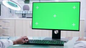 Mãos masculinas do doutor que datilografam no computador com a tela do verde do modelo video estoque