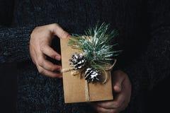 Mãos masculinas do fundo do Natal que guardam o fundo escuro do presente caseiro do Natal fotografia de stock