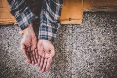 Mãos masculinas do mendigo que procuram o dinheiro, moedas da bondade humana imagem de stock