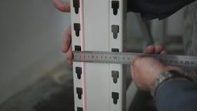 Mãos masculinas do ` s com a ferramenta de medição da precisão Coordenador Makes Measurement do feixe no armazenamento, fim acima video estoque