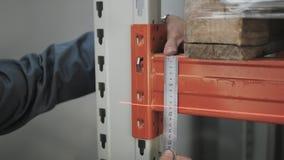 Mãos masculinas do ` s com a ferramenta de medição da precisão Coordenador Makes Measurement do feixe no armazenamento, fim acima filme