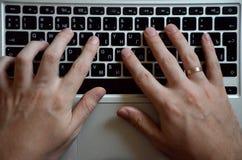 Mãos masculinas em um teclado preto Trabalho europeu em um computador fotos de stock