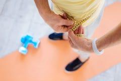 Mãos masculinas lisas que medem a cintura Fotografia de Stock