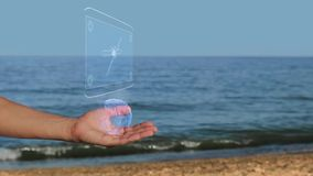 Mãos masculinas na praia com satélite do holograma filme