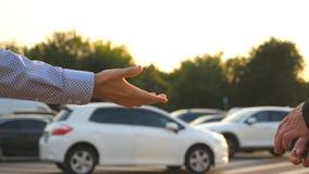 Mãos masculinas no terno que dá chaves do carro a seu amigo O braço do homem de negócios passa a chave do carro Aperto de mão ent vídeos de arquivo
