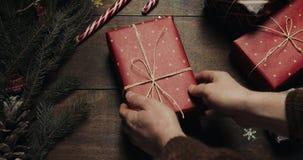 Mãos masculinas postas para dar o presente grande do ano novo sobre o fundo de madeira do estilo com a decoração do ano novo e a  vídeos de arquivo