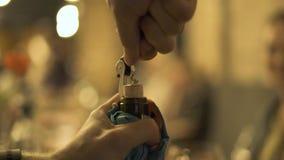 Mãos masculinas que abrem a garrafa de vinho com o corkscrew no fim da tabela do feriado acima O homem que usa a cortiça para des vídeos de arquivo