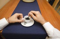 Mãos masculinas que agitam o café do café em um copo Imagens de Stock