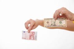 Mãos masculinas que comparam duas cédulas - euro e dólares Fotos de Stock Royalty Free