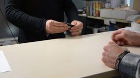 Mãos masculinas que dão o cartão de crédito ao outro homem filme