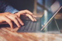 Mãos masculinas que datilografam na estação eletrônica da teclado-doca da tabuleta Equipe o trabalho no escritório ao sentar-se n fotos de stock royalty free